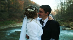 bride and groom kissing on the background of the forest river - stock footage
