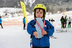 Portrait of young preschool boy, with medal for ending a ski school - stock photo