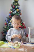 Cute little boy, playing with modeling dough, molding figures at home on Chri Stock Photos