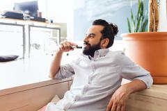 Stock Photo of smiling man with beard and hair bun at office