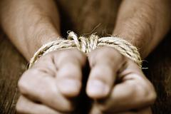 The hands of a young man tied with rope Stock Photos