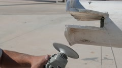Worker sanding yachts mast with angle grinder. Close up Stock Footage