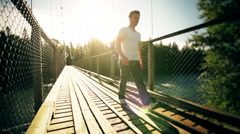 Motion-Photo (Cinemagraph) of a Young Man Crossing a Solid Hanging Bridge over Stock Footage