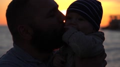 Father kissing baby during sunset Stock Footage