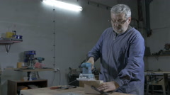 Man sanding and grinding edges of board with electric sander, low angle. Stock Footage