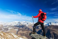 Hiker takes a rest admiring the mountain landscape. Sunny day, early winter.  - stock photo