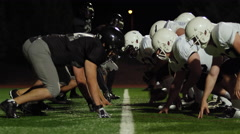 A football player gets tackled on his way to the end zone at night Stock Footage