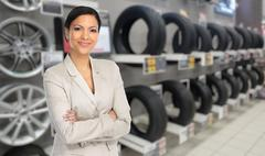 Auto dealer woman near a car tire. - stock photo