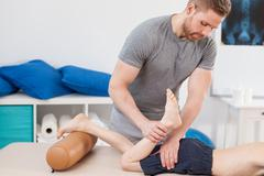 Chiropractor stretching boy's leg Stock Photos