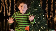 Cute Child Excitedly Dances in Front of Christmas Tree Stock Footage
