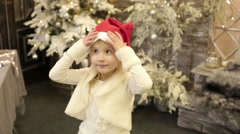 A beautiful small girl takes off Santa hat. Merry Christmas and Happy new year. Stock Footage