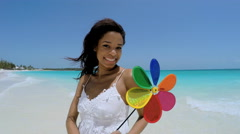 Selfie portrait smiling African American girl holding toy pinwheel on beach Stock Footage