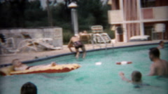 1955: Dad playing with kids in hotel pool with inflatable raft. - stock footage