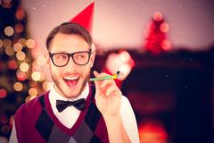 Stock Photo of Composite image of geeky hipster in party hat with horn