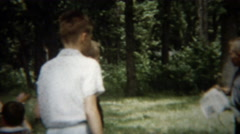 1955: Boys tending campfire during the warm summer day in the park. Stock Footage