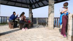 Tourists look at smartphones ignore breathtaking panorama at Yehliu cape edge Stock Footage