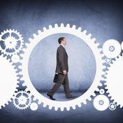 Businessman walking in cog wheel Stock Photos