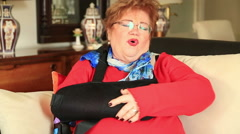 Mature woman with a broken arm wearing arm brace Stock Footage
