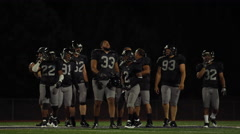 A football team walking on the field at night Arkistovideo