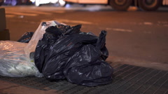 City sidewalk with trash bags on curb at night 4k Stock Footage