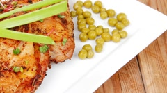 Chicken legs garnished with green peas and hot chili peppers  Stock Footage