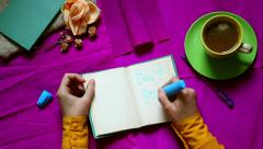 Hands writing and painting Don't stop. Top view. Purple background from above Stock Footage