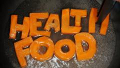 Words Healthy Food collected from letters, which are carved from carrots Stock Footage