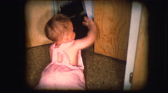 Vintage 8mm footage of a child opening cupboard - stock footage