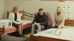 The consultant helps to choose to a couple a mattress Stock Footage