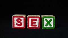 "Slow Motion - Condom falls/thrown near Alphabet Blocks spelling the word ""Sex"". Stock Footage"