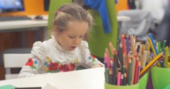 Little Blonde Girl is Sitting at Table And Cutting Out a Figure from Green Stock Footage