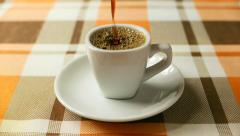 freshly brewed black coffee is poured into a porcelain cup - stock footage