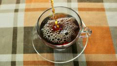 Hot black tea is poured into a transparent cup and saucer, slow motion Stock Footage
