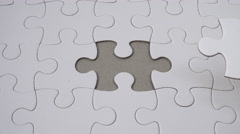 Hand completing empty white jigsaw puzzle. Top down view. Conceptual abstract sh - stock footage