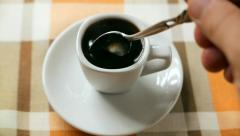 In freshly brewed black coffee is added and stirred sugar in porcelain dish Stock Footage