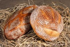 white loaf two different forms lying in the straw on gray linen tablecloth - stock photo