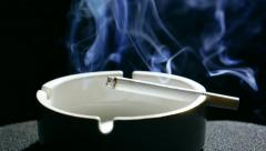 Stock Video Footage of Smoldering cigarette in the ashtray with ash, nicotinic blue smoke. Smoking