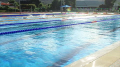 Swimmers Training In Outdoor Olympic Size Swimming Pool Lens Flare Slow Motion Stock Footage