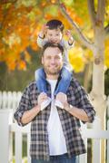 Happy Mixed Race Boy Riding Piggyback on Shoulders of Caucasian Father. Stock Photos