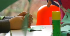 Stock Video Footage of Kids Are Working With Colorful Paper Childish Hands Glue Making a Paper Toy