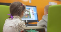 Little Girl is Observing a Boy is Playing Computer Game Children Are Sitting at - stock footage