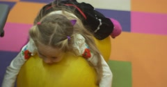 Little Blonde Girl is Lying With Her Belly on Two Yellow Balls and Falling Down - stock footage