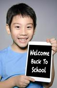 Little asian boy smiles with tablet computer  With Back to School Text Writte - stock photo