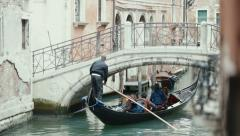 VENICE, ITALY - Sep 2013: A gondolier navigates his gondola under a bridge on a Stock Footage