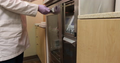Dental Technician Loading Container in Washer - stock footage
