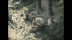 Vintage 16mm film, 1960, Austria, woman washing clothes in stream Stock Footage