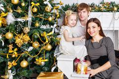 Family near the Christmas tree and gifts. - stock photo
