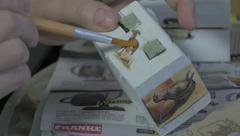 Female artist sticking photos on box with brush and glue, close up, decoupage. Stock Footage