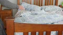 A dolly shot of a man making the bed in the morning Stock Footage