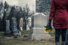 Close-up of a Sad in front of a Gravestone. - stock photo
